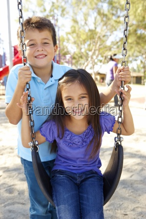 boy and girl playing on swing