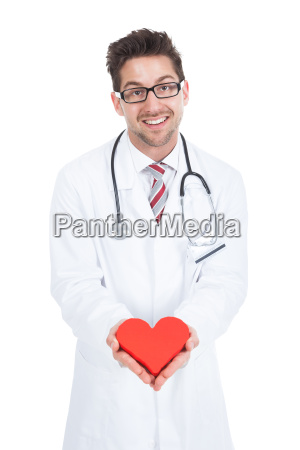 confident young male doctor holding heart