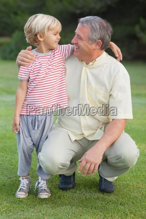 grandfather crouching beside grandson looking at