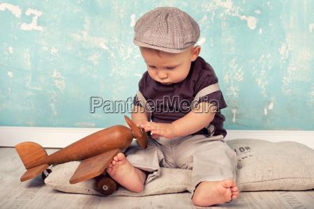 kleiner junge spielt mit holzflieger