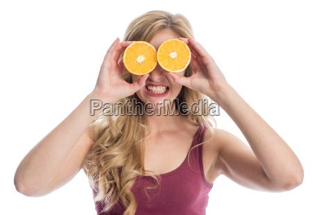 frau mit orangenscheiben auf den augen