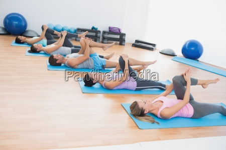 sporty people stretching legs in fitness