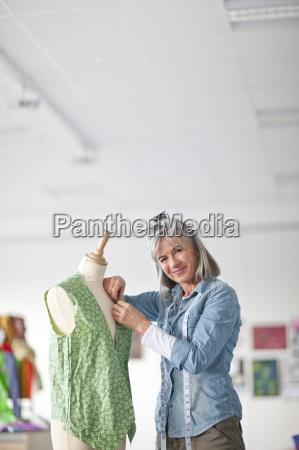 smiling designer adjusting shirt on dressmakerx2019s