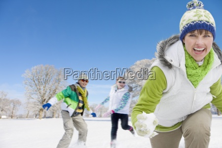 mother and children throwing snowballs in