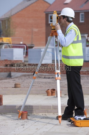 surveyor using theodolite at construction site