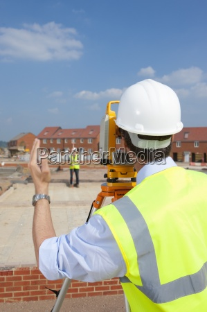 surveyor behind theodolite gesturing to co