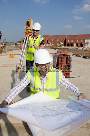 surveyor and architect with blueprints and