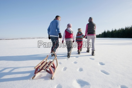 family walking and pulling sled in