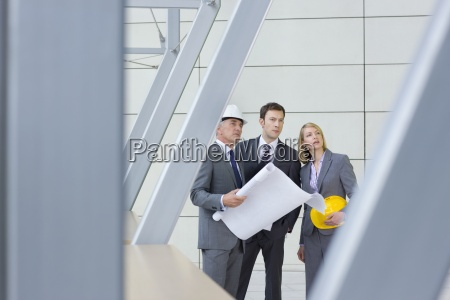 architects and engineer holding blueprints in