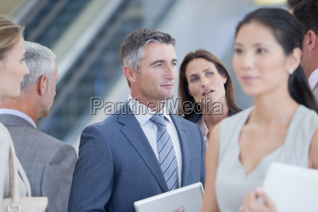 serious businessman listening to co worker