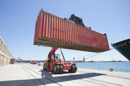 mobile crane moving container ship at
