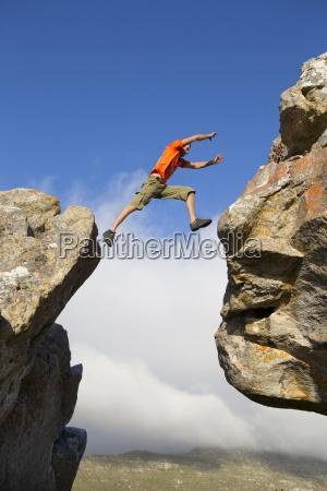 maennlich kletterer springt zwischen felsen