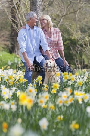 smiling senior couple with dog leaning