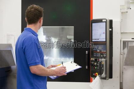 technician with clipboard watching lathe cutting