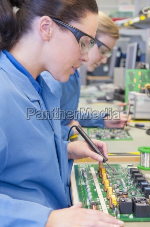 close up of technicians soldering circuit