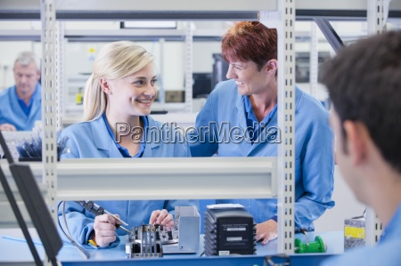 smiling supervisor and technician assembling circuit