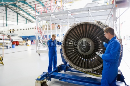 engineers assembling engine of passenger jet