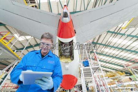 engineer with digital tablet below tail