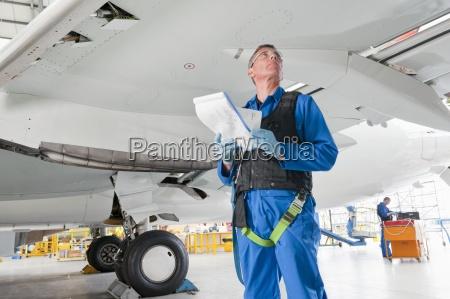 engineer with paperwork below wing of