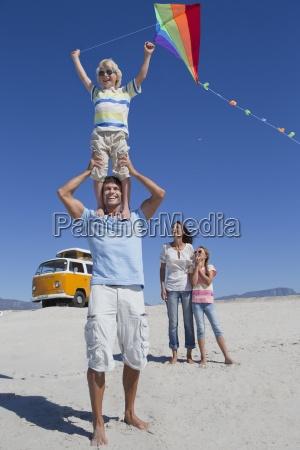 happy family flying kite on sunny