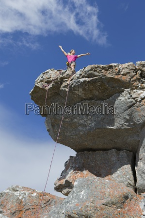 female rock climber standing on top