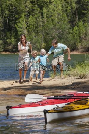 family running toward kayaks at lakeside