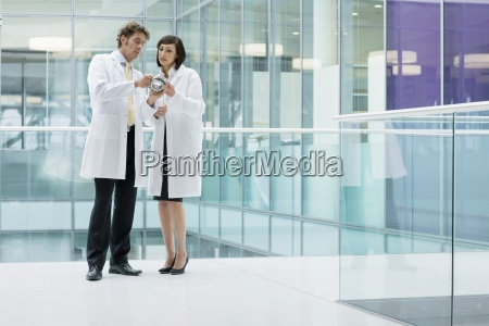 engineers in lab coats examining part