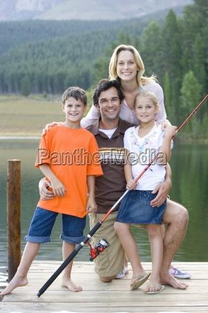 vierkoepfige familie mit angelrute auf jettylaechelnportrait
