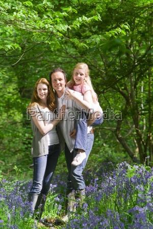 family posing in field of bluebell