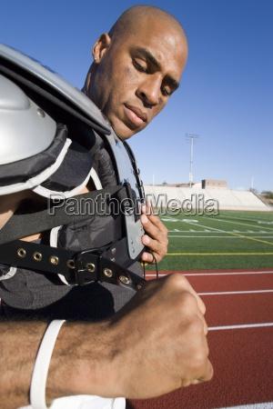 american football player adjusting protective shoulder