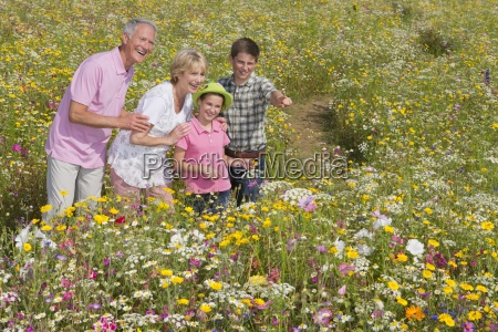 smiling grandparents and grandchildren standing among
