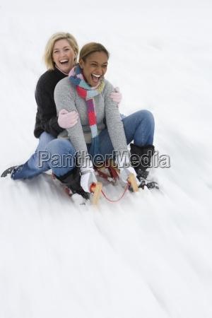 women sledding down snow slope