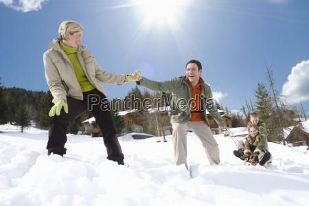 young family sledding in snow on