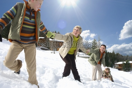 young family holding hands and sledding