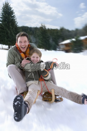 father and daughter sledding down snow