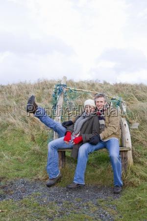 couple sitting on bench enjoying outdoors