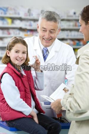 apotheker hilft maedchen mit asthma inhalator