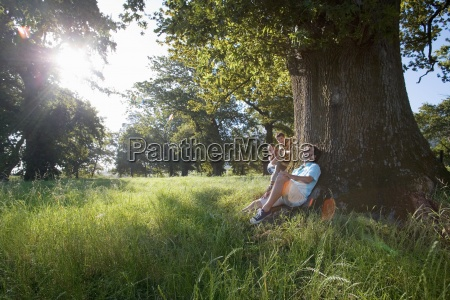 man resting against tree mischievous son
