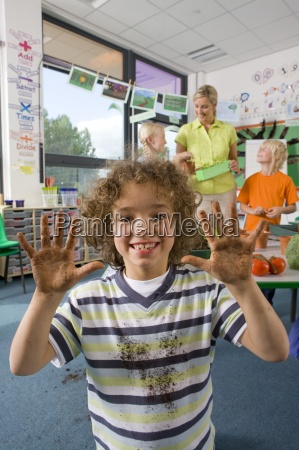 smiling boy studying biology in classroom
