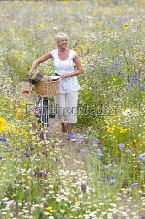 woman pushing bicycle on path through