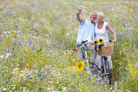 senior couple on bicycles in field