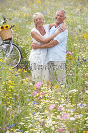 smiling senior couple standing in field