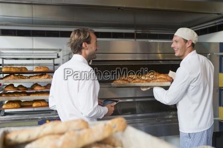 baker holding bread in bakery kitchen