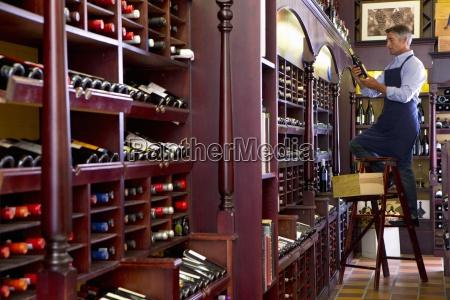 worker on ladder stocking bottles in