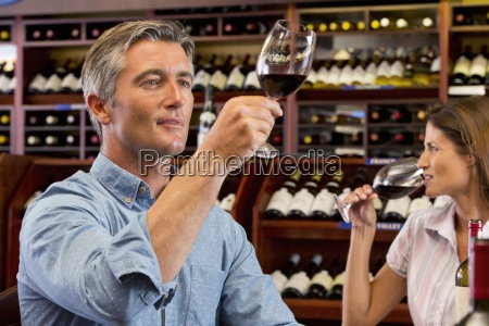 curious couple examining glasses of red