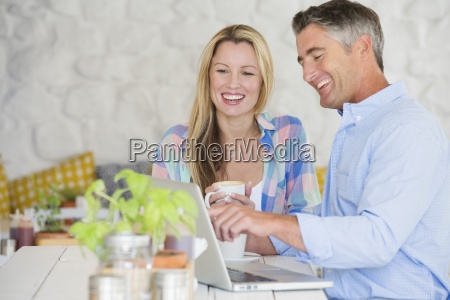 couple with coffee using laptop at
