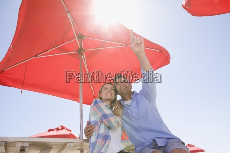 smiling couple pointing up under umbrella
