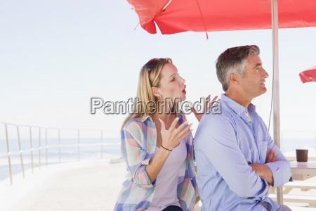 couple arguing under umbrella at waterfront