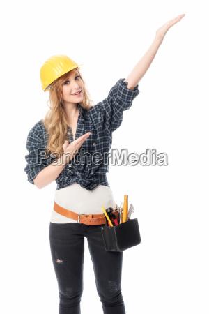 weiblicher handwerker mit bauhelm zeigt nach