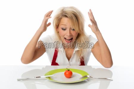 frau sitzt vor einer tomate auf